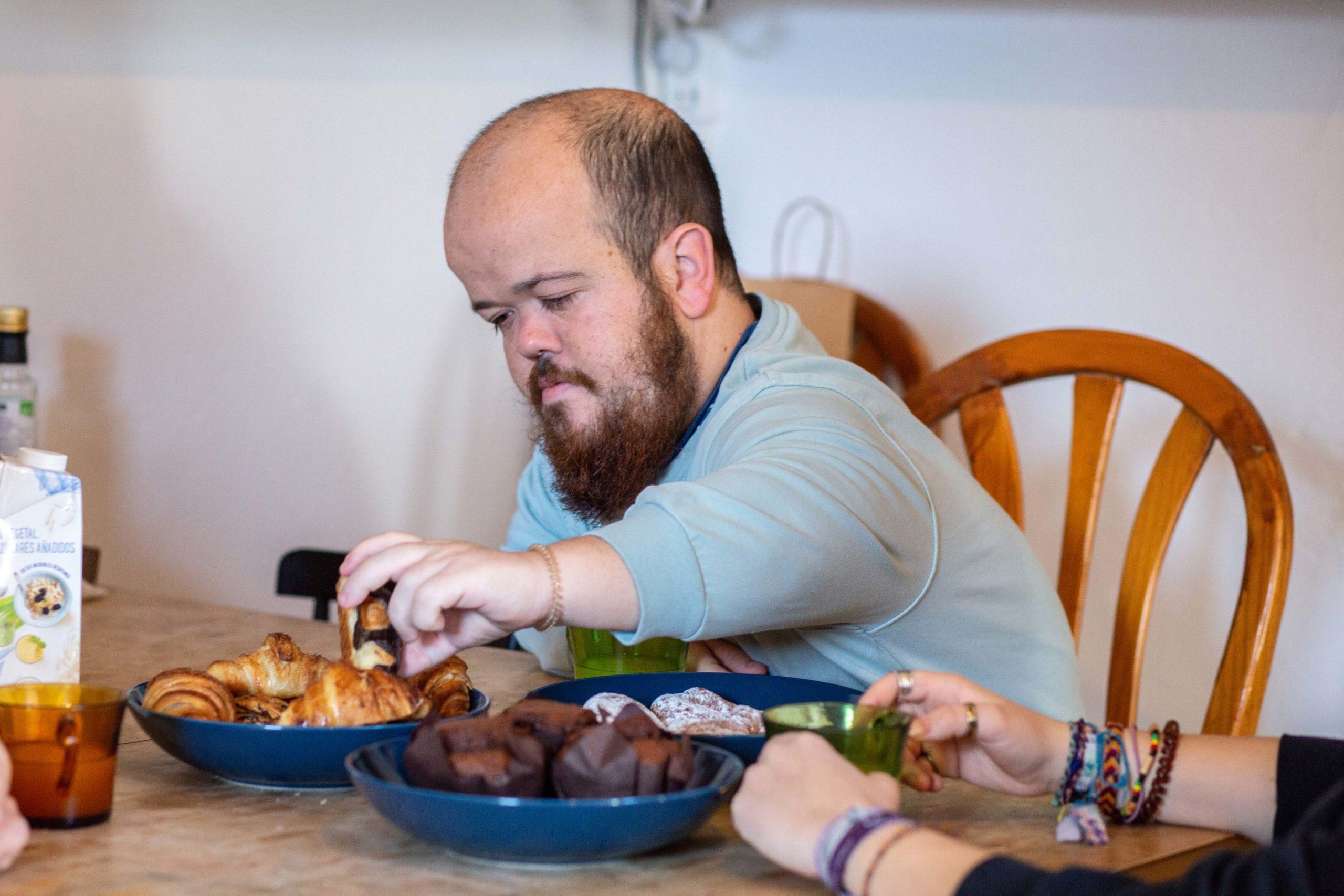 Un noi agafant un croissant d'un plat de la taula del menjador