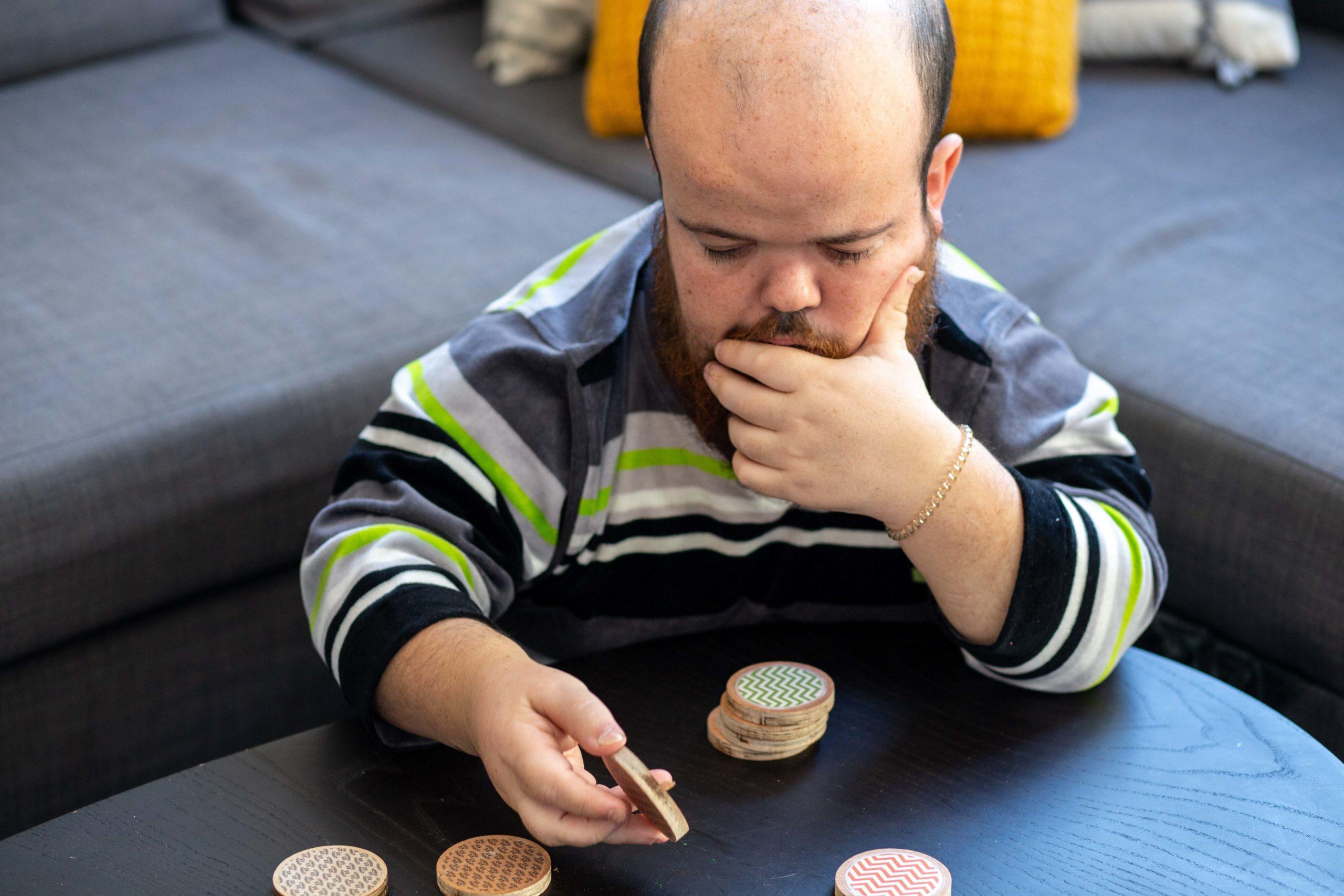 Un noi pensant en quina peça utilitzar del joc de taula al que està jugant al menjador