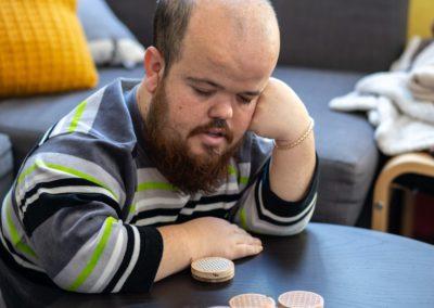 Un noi pensant mentre juga a un joc de taula