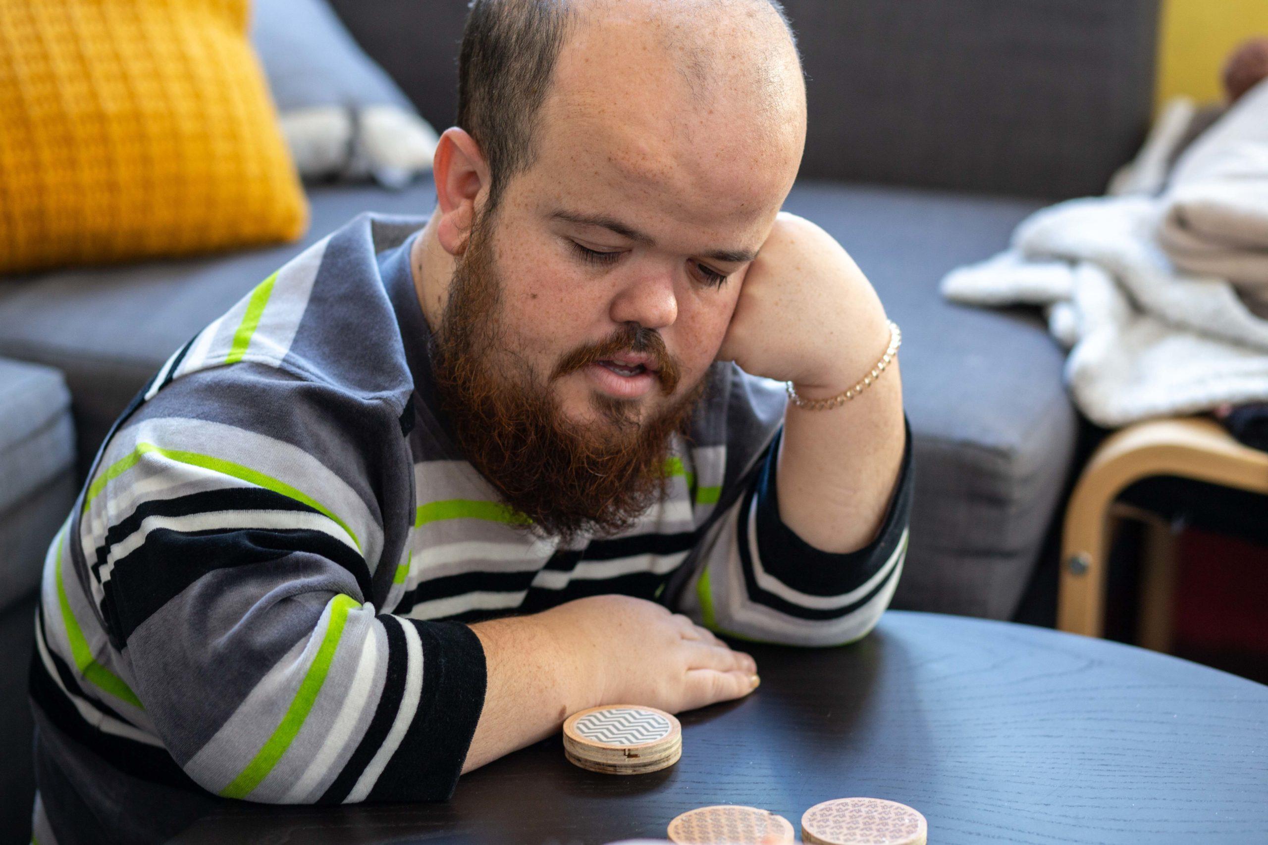 Un noi pensant mentre juga a un joc de taula al menjador