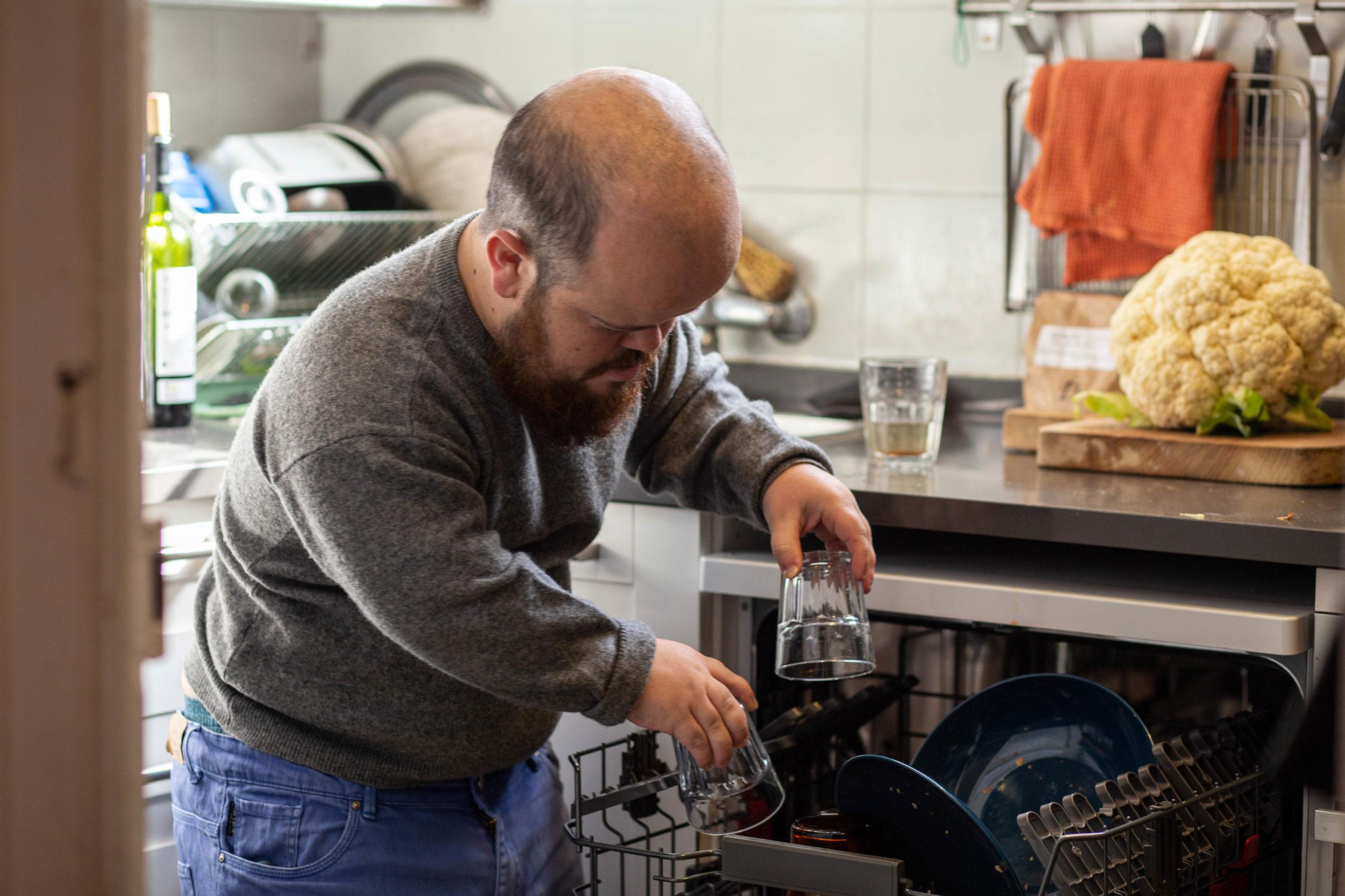 Un noi posa els plats dins del rentavaixelles a la cuina