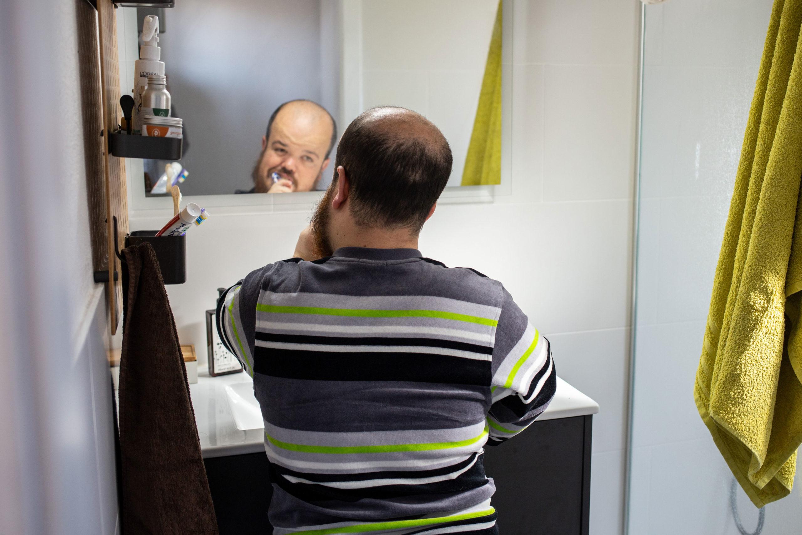 Un noi es raspatlla les dents mentre es mira al mirall del lavabo
