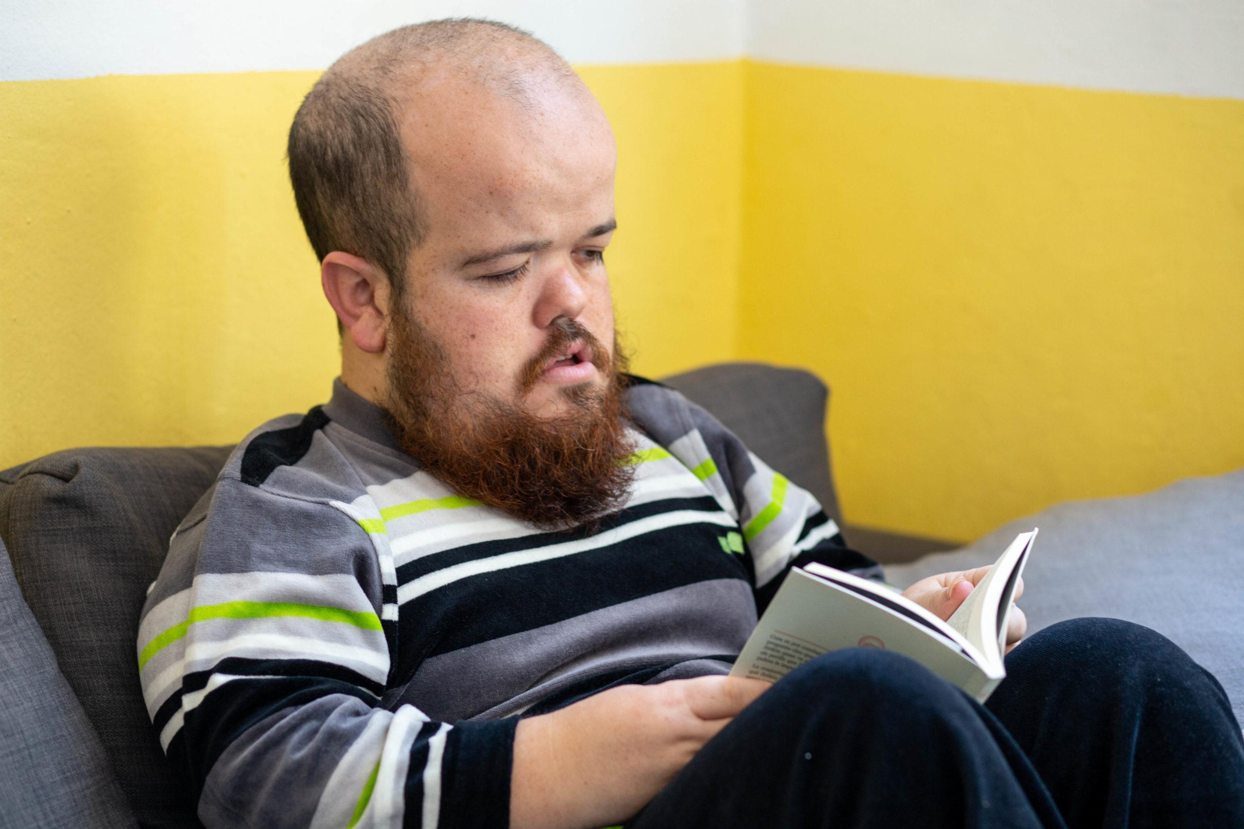 Un noi està llegint un llibre assegut al sofà del menjador