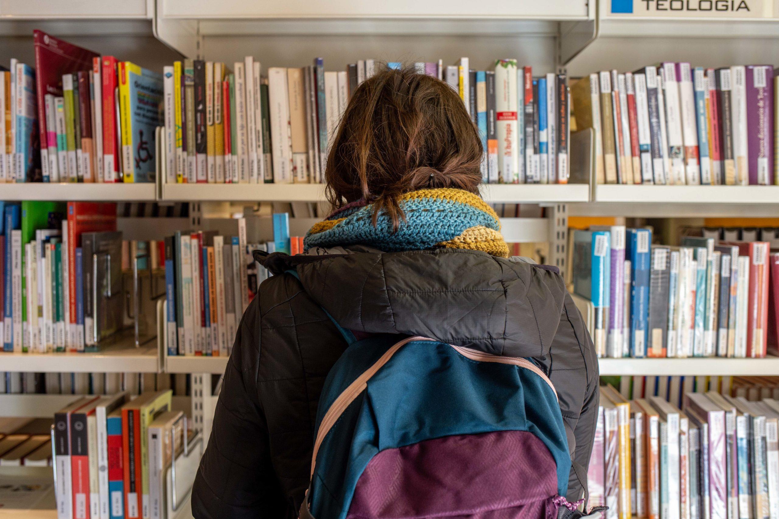 Noia davant prestatgeria de llibres