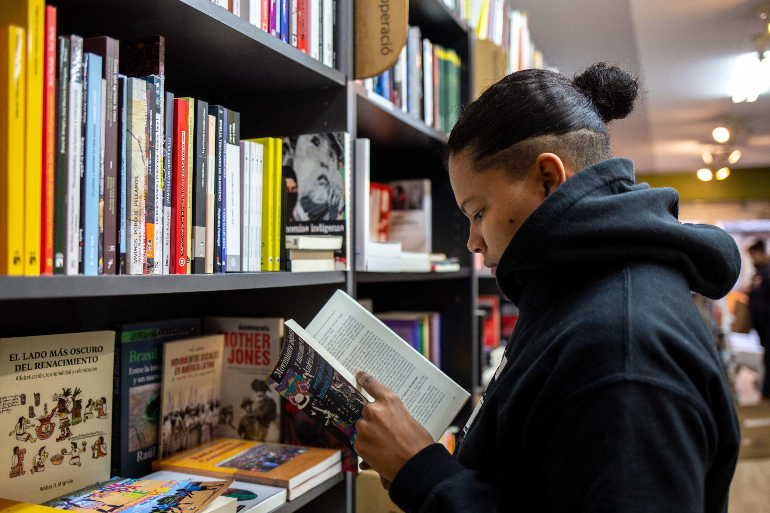 Noia llegint a llibreria