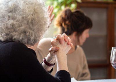 Dona de perfil asseguda amb les mans creuades i dona de fons