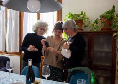 Tres dones mirant el mòbil al menjador de casa
